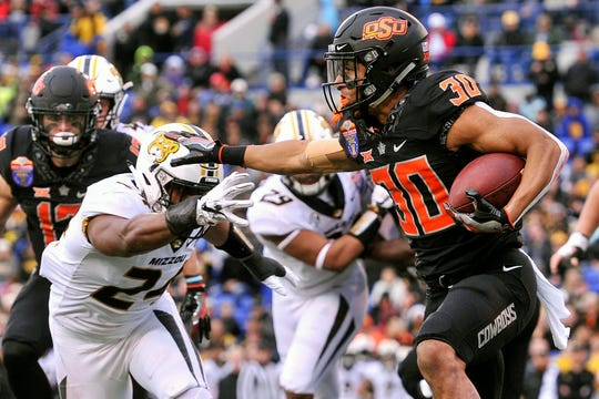 Dec 31, 2018; Memphis, TN, USA; Oklahoma State Cowboys running back Chuba Hubbard (30) carries the ball against Missouri Tigers linebacker Terez Hall (24) during the first half in the 2018 Liberty Bowl at Liberty Bowl Memorial Stadium. Mandatory Credit: Justin Ford-USA TODAY Sports