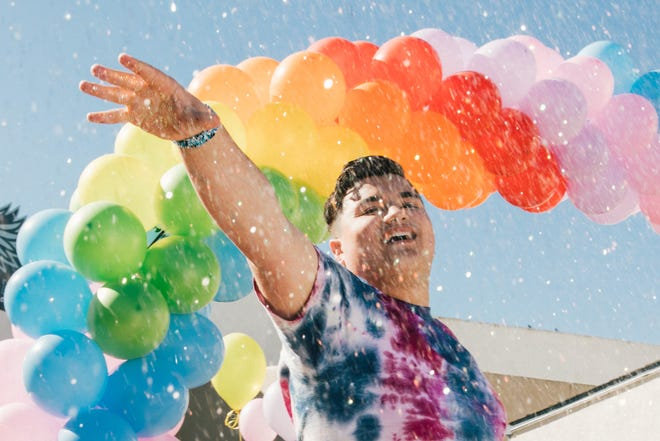 Zeke Ibarra Sumpter strikes a pose at his high school under an arch of rainbow-colored balloons.