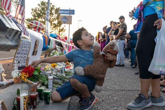 Noah Escarcega, 7, lays flowers with his mother and prays for the victims and their families outside Walmart in El Paso, Texas., on Aug. 6th, 2019. The mass shooting claimed 22 lives inside and outside the Walmart; 25 others were injured.