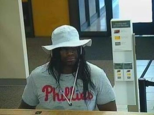 Security footage shows a person police believe to be Michael Wheeler of Wilmington, wearing a wig, Phillies shirt, blue cargo shorts and a bucket hat as he robbed the Wells Fargo bank on West Chester Pike in Bloomall, Pennsylvania.