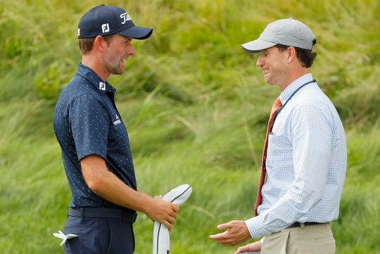 Webb Simpson, left, speaks with an official on the 12th hole.