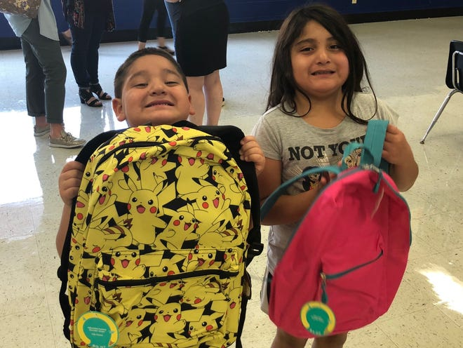 Jose and Thalia Aragon show off their new backpacks at Reagan Elementary Friday. They, along with every other Reagan Elementary student, received a free backpack thanks to a donation from Walmart and State Sen Dawn Buckingham.