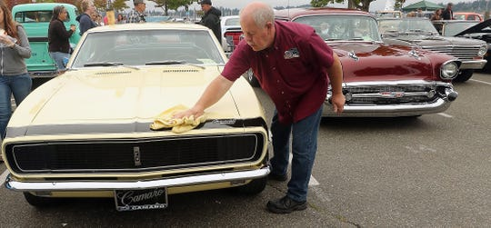 Mike Elliott, of Port Angeles wipes the moisture off of his wife Tomi's 1967 Chevy Camaro as they take part in the Cruz on the Port Orchard Waterfront on Sunday, August 11, 2019.