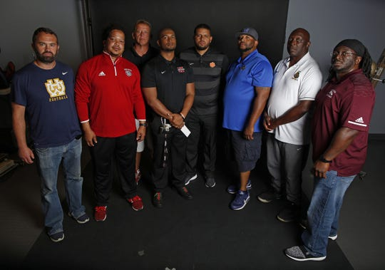 Head football coaches from Cincinnati-area high schools include, from left, Gerry Beauchamp of Walnut Hills, Ben Nevels of Holmes, Arvie Crouch of Mt. Healthy, Chris Mobley of Hughes, Kali Jones of Withrow, Greg Conwell of Woodward, Jeff Cargile of Taft and Armand Tatum of Western Hills. This guard is among the Greater Cincinnati coaches who make a three-month season a year-long job looking out for their boys.