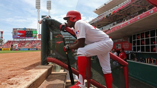 Cincinnati Reds' Aristides Aquino watches the game from the dugout during the third inning of a baseball game, against the Chicago Cubs Sunday, Aug. 11, 2019, in Cincinnati.
