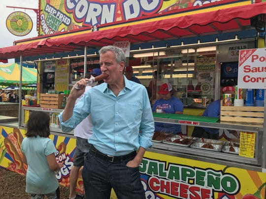 New York City Mayor Bill de Blasio eats a corn dog at the Iowa State Fair on Sunday.