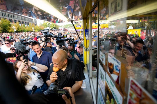 New Jersey Senator and 2020 Democratic presidential candidate Cory Booker tries a fried peanut butter and jelly sandwich during the Iowa State Fair on Saturday, Aug. 10, 2019 in Des Moines.