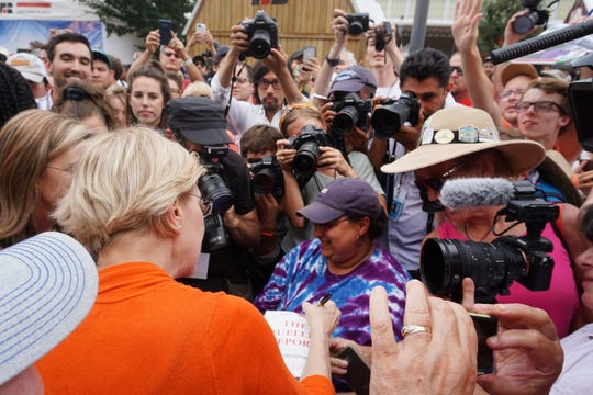 2020 candidate Elizabeth Warren signs a copy of The Mueller Report after her soapbox speech at the Iowa State Fair Aug. 10, 2019.
