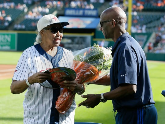 Minnie Forbes, former owner of the Detroit Stars of the Negro Leagues, is presented with flowers by former Detroit Tiger Jake Wood, right, during a celebration of the Negro Leagues before the Tigers' baseball game against the Kansas City Royals on Saturday, Aug. 10, 2019, in Detroit.