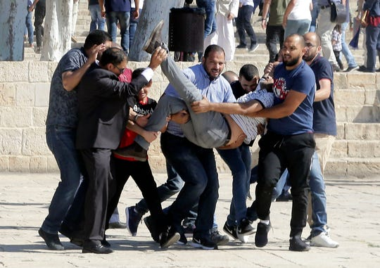 Palestinians carry injured person during clashes with Israeli police at al-Aqsa mosque compound in Jerusalem, Sunday.