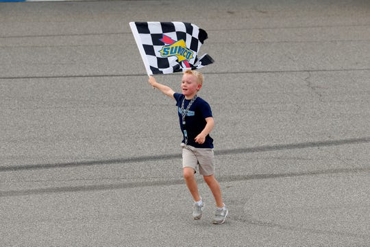 Kevin Harvick's son, Keelan, runs with the checkered flag after Sunday's race.