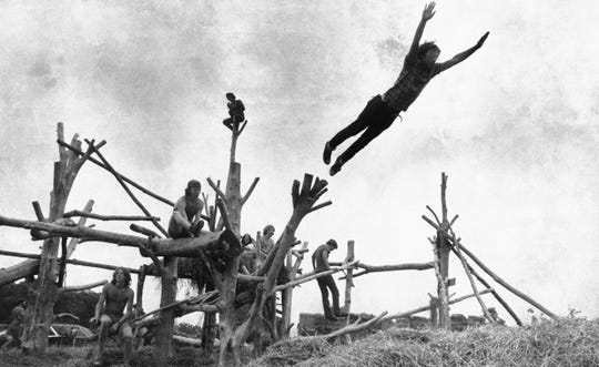 Rock music fans sit on a tree sculpture as one leaps mid-air onto a pile of hay during the Woodstock Music and Art Festival held in Bethel, N.Y. on Aug. 15, 1969.