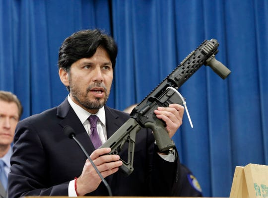 In this Jan. 13, 2014 file photo, former California State Sen. Kevin de Leon, D-Los Angeles, displays a homemade fully automatic rifle, confiscated by the Department of Justice, at the Capitol in Sacramento, Calif.