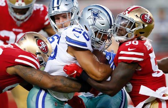 Cowboys running back Darius Jackson runs between 49ers Damontre Moore, left, and LaRoy Reynolds.