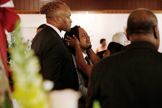 A relative attempts to console Dion Green, center, before the funeral for his father, Derrick Fudge, on Saturday, Aug. 10, 2019, at a church in Springfield, Ohio.