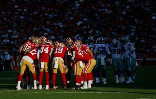 San Francisco 49ers offensive players huddle during the first half of the team's preseason game against the Dallas Cowboys.