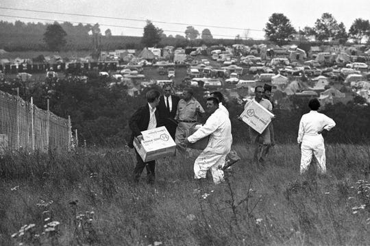 In this Aug. 17, 1969 file photo, workers carry medical supplies that arrived by helicopter on the grounds of the Woodstock Music and Art Festival in Bethel, N.Y.