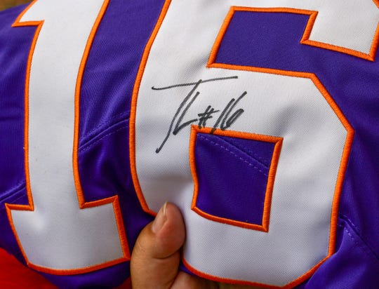 A fan holds up a jersey with quarterback Trevor Lawrence's autograph during Clemson football Fan Appreciation Day in Memorial Stadium Sunday, August 11, 2019.