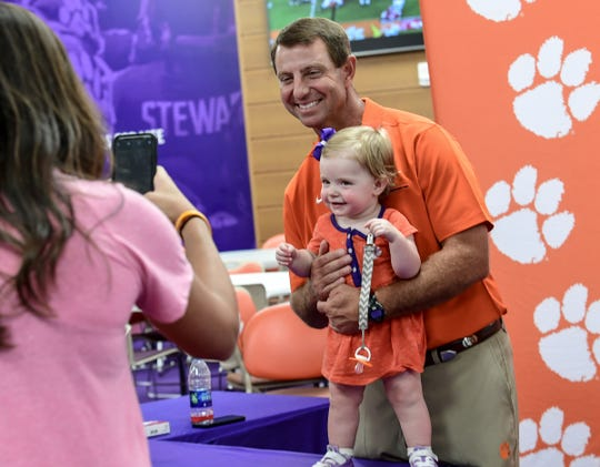 Ryleigh Potford poses with Clemson Head Coach Dabo Swinney during Clemson football Fan Appreciation Day in Memorial Stadium Sunday, August 11, 2019.