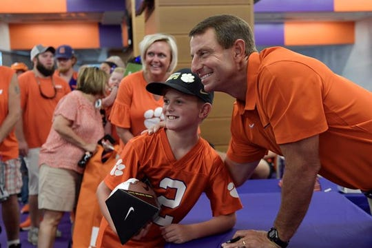 Dabo Swinney poses with Michael Scott of Aiken and his mom April Scott during Fan Appreciation Day at Memorial Stadium in Clemson Sunday, Aug. 11, 2019. Thousands came to get autographs and pictures of their favorite players and coaches and to meet the Clemson Tiger mascot.
