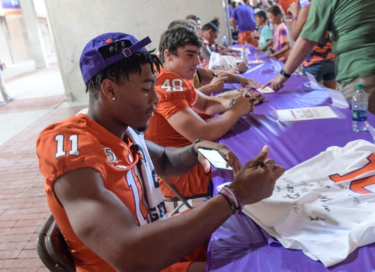 Clemson safety Isaiah Simmons (11) signs autographs during Clemson football Fan Appreciation Day in Memorial Stadium Sunday, August 11, 2019.