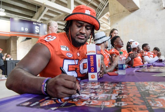Clemson defensive lineman Jordan Williams (59) signs an autograph during Clemson football Fan Appreciation Day in Memorial Stadium Sunday, August 11, 2019.