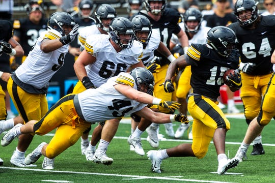 Iowa linebacker Dillon Doyle (43) tackles running back Tyler Goodson (15) during a Hawkeyes football Kids Day scrimmage, Saturday, Aug. 10, 2019, at Kinnick Stadium in Iowa City, Iowa.