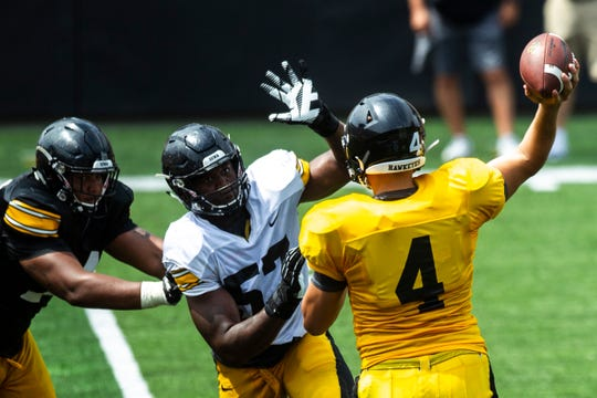 Three prominent players are pictured in this photo: offensive tackle Tristan Wirfs (in black), defensive end Chauncey Golston (white) and quarterback Nate Stanley (gold).