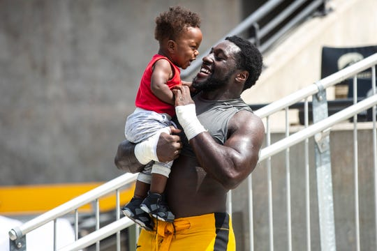 Iowa defensive end Amani Jones laughs while holding son Amani Jr. after the Hawkeyes' Kids Day practice Aug. 10.