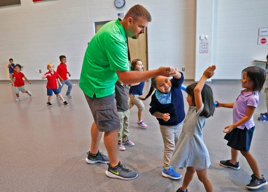 Physical Education teacher Adam Schott plays a running game with students at Jeremiah Gray Kindergarten Academy, Friday, August 2, 2019.