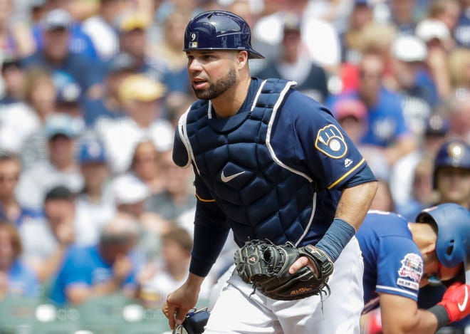 Brewers catcher Manny Pina walks back to the dugout after the end of the top of the first inning.