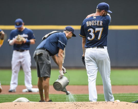 Brewers starting pitcher Adrian Houser recomposes himself after he became ill and strikes out 10 betters in six innings.