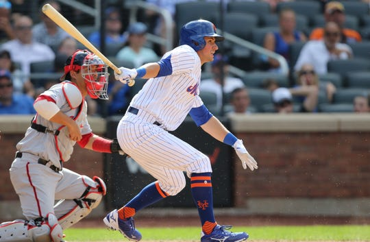 Joe Panik gets a base hit while playing for the New York Mets against the Washington Nationals in Queens.