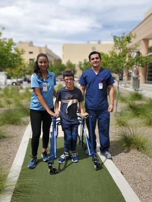 Jacob Avalos, who suffers from cerebral palsy and recently underwent surgery to help him walk, is aided by Carrie Tingley rehab technicians Elena Vigil, left, and Brian Lopez at the University of New Mexico Children's Hospital in Albuquerque.