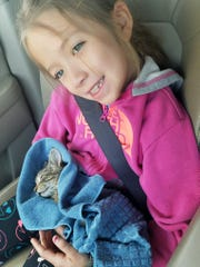 Rayna Souverbrielle, 9, gives comfort to a kitten her family will be fostering.