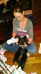Candice Souverbielle bottle feeds a litter of pups the family fostered.