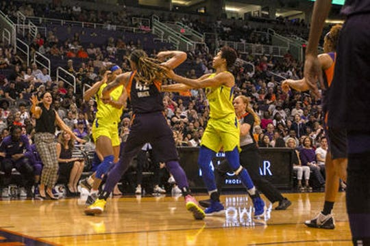 Phoenix Mercury center Brittney Griner responds to being hit in the head by Dallas Wings' forward Kristine Anigwe in the fourth quarter Saturday night.