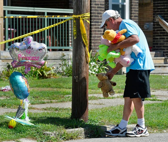 Paul Laughlin, 57, places stuffed animals on Sunday, Aug. 11, 2019 outside a home at 1248 West 11th St. in Erie, Pa., where multiple people died in an early-morning fire.   (Greg Wohlford/Erie Times-News via AP)