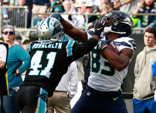 Seattle Seahawks' David Moore (83) catches a pass as Carolina Panthers' Captain Munnerlyn (41) defends.