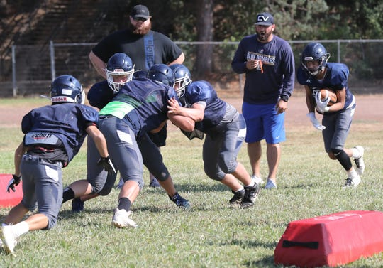 Central Valley head varsity football coach Aaron Richards, second from right, leads a drill during practice on Friday, Aug. 9, 2019.