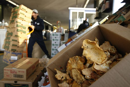 An open box of chanterelle mushrooms, right, is seen at the Wholesale Produce Market in downtown Los Angeles.