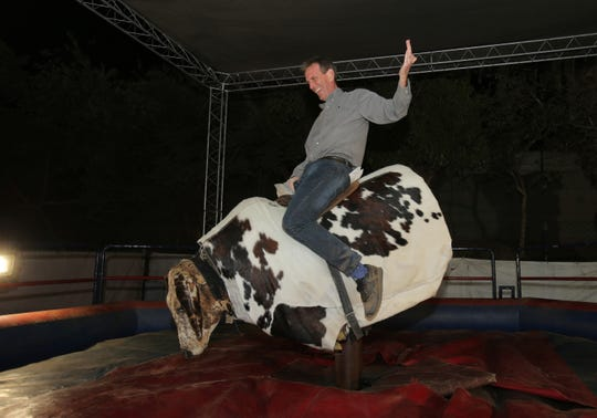 Ventura County Star reporter Tom Kisken rides the mechanical bull during the Ventura County Fair on Saturday.