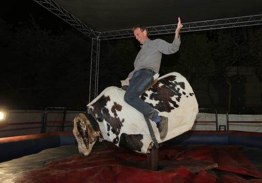 Ventura County Star reporter Tom Kisken rides the mechanical bull during the Ventura County Fair on Aug. 10, 2019.
