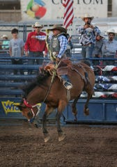 Saddle Bronc rider Joaquin Real of Santa Paula goes for a spin at Saturday night's rodeo during the final weekend of the Ventura County Fair.