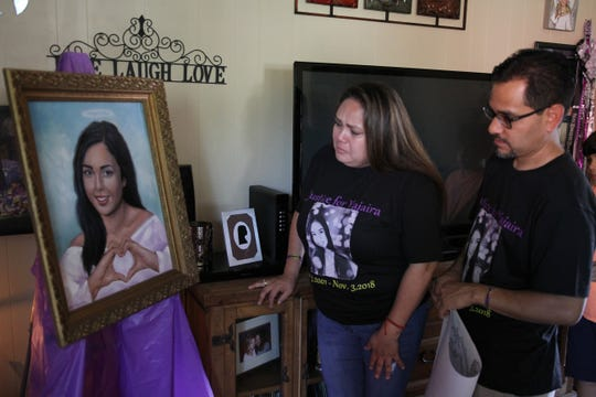 Mayela and Ramiro Garcia become emotional as they look at the portrait of their daughter Yajaira in this Aug. 10, 2019, file photo taken at the home of Bianka and Vern Landavazo, whose 13-year-old daughter Lauren was murdered in 2016.