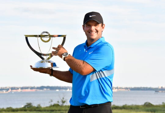 Patrick Reed poses with his trophy after winning The Northern Trust golf tournament at Liberty National Golf Course.