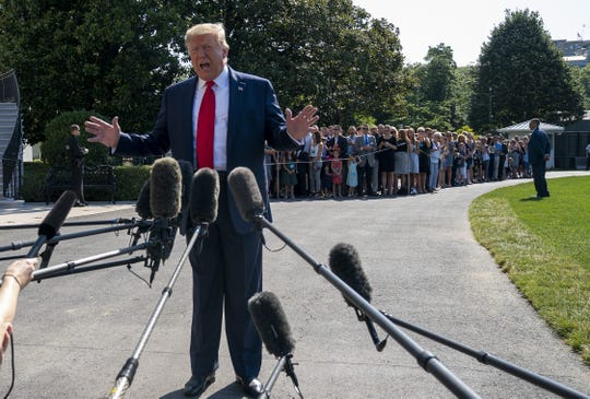 President Donald Trump speaks to members of the press before departing from the White House on the south lawn before he boards Marine One on August 09, 2019