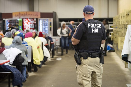 This image released by the US Immigration and Customs Enforcement (ICE) shows a Homeland Security Investigations (HSI) officer guarding suspected undocumented workers on August 7, 2019. Officers detained approximately 680 people at plants across Mississippi.