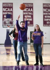 Bryce Weiler, a blind manager for Evansville's men's basketball team, demonstrates how he shoots free throws with help from friend Janelle Gore, right, in a 2013 photo.