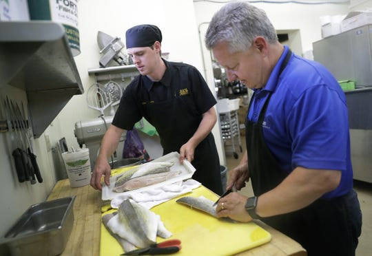 Majority owner Mark Dougherty, right, and Alex Shea, head chef and new partner, work in the kitchen at Mark's East Side in Appleton.